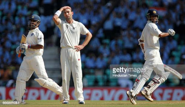 Indian batsmen Rahul Dravid and MS Dhoni take a run as New Zealand bowler Andy McKay looks in disgust on the second day of the third test match...