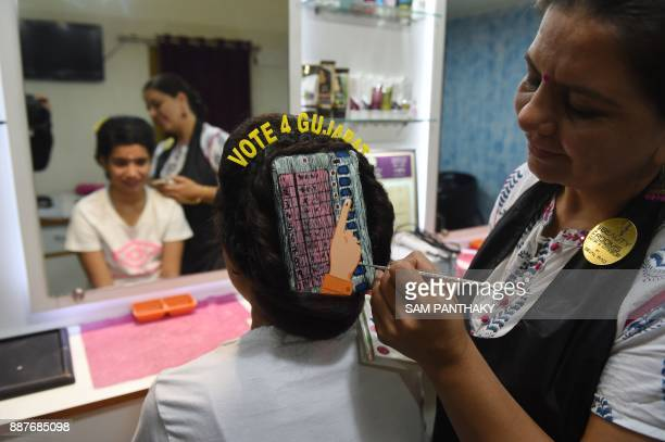Indian beautician Sejal Rao gives finishing touches as she paints 'Electronic Voting Machine' on the hair of a girl ahead of Gujarat's legislative...