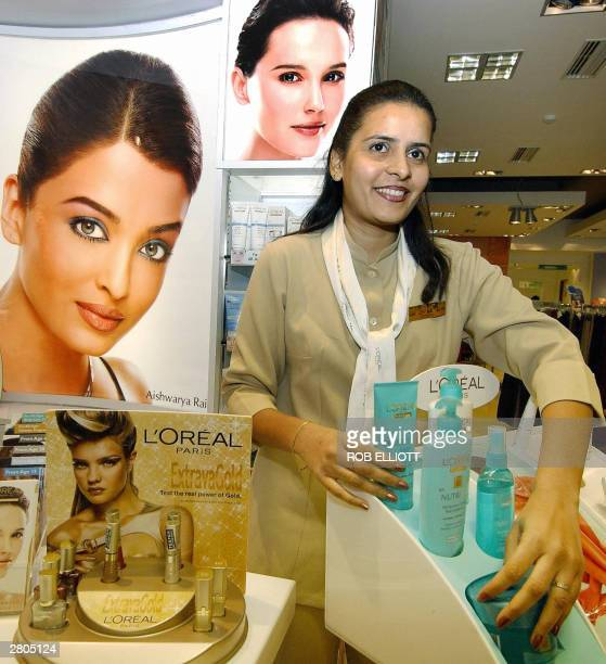 Indian beauty advisor Aziza Mistry sets up her L'oreal Paris cosmetics stand in front of a poster of Indian film actress Aishwariya Rai inside in...