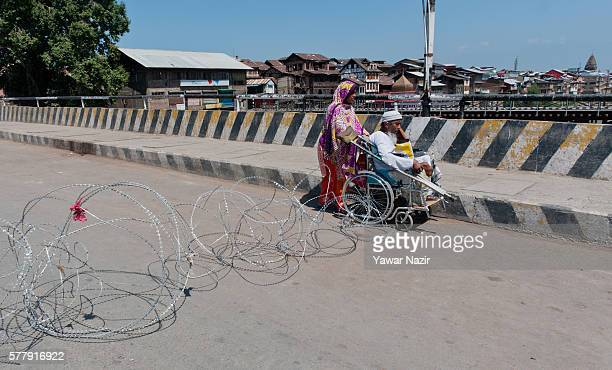 Indian beggars cross a concertina wire of Indian government forces during a curfew following violence that has left over 45 people dead and thousands...