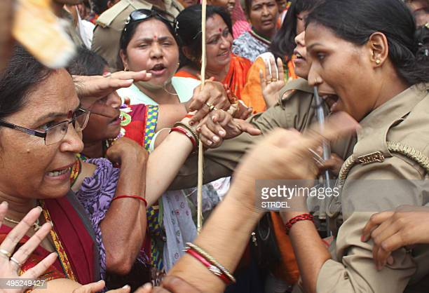 Indian Bharatiya Janata Party demonstrators argue with policewomen during a protest against the recent gangrape and murder of two girls in Lucknow on...