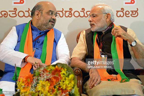 Indian Bharatiya Janata Party national president Amit Shah and Prime Minister Narendra Modi talk during a BJP office bearers' meeting held on the eve...