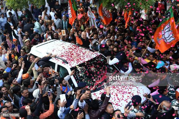 Indian Bharatiya Janata Party President Amit Shah show the victory sign to supporters as he arrives to address a press conference at the party...