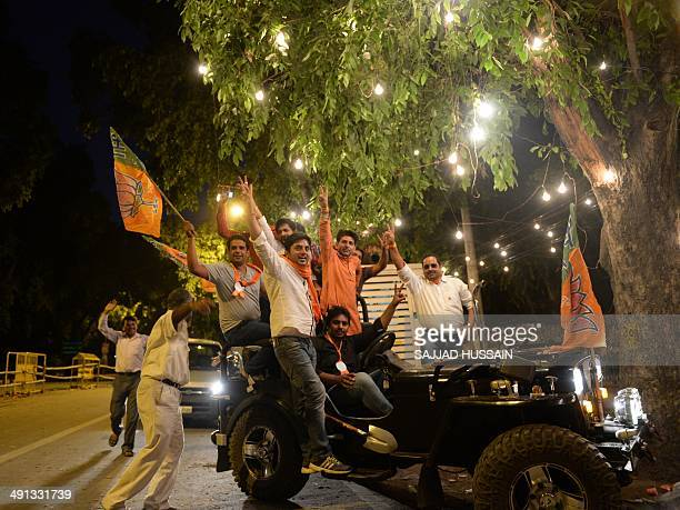 Indian Bharatiya Janata Party supporters gesture from a jeep outside the BJP headquarters in New Delhi on May 16 2014 India's triumphant Hindu...