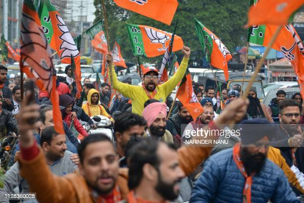Indian Bharatiya Janata Party workers hold BJP flags during a 'Vijay Sankalp' bike rally in Amritsar on March 2 2019 Cranking up its campaign for the...