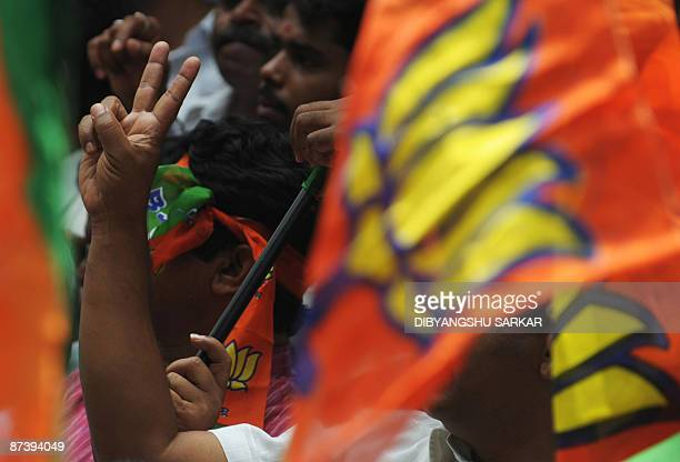 Indian Bharatiya Janata Party workers wave flags as they celebrate the victory of their party candidate in the Bangalore South parliamentary seat on...