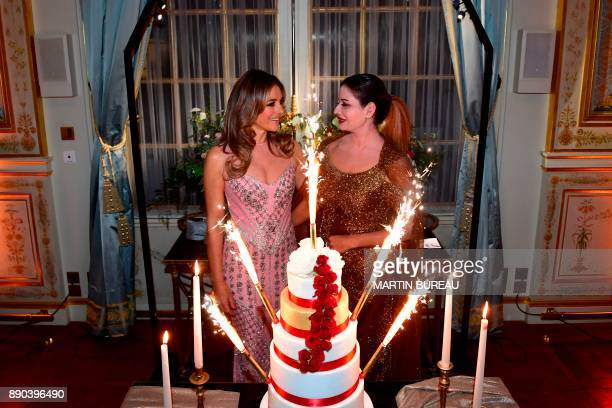 Indian billionaire Sudha Reddy stands with British actress Liz Hurley behind a cake in Paris on December 11 2017 during a charity dinner in Reddy's...