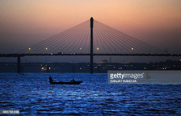 Indian boatman make their way at Sangam the confluence of the rivers Ganges Yamuna and the mythical Saraswati in Allahabad on March 10 2015 AFP PHOTO...