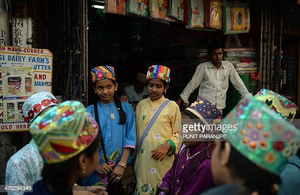 Indian Bohra Muslim girls clad in multicoloured headgear interact outside their mosque in Mumbai on February 19 2014 The Bohra brand of Islam is...