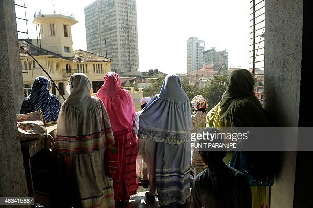 Indian Bohra Muslim women watch the funeral procession of their spiritual leader Syedna Mohammed Burhanuddin in Mumbai on January 18 2014 A stampede...