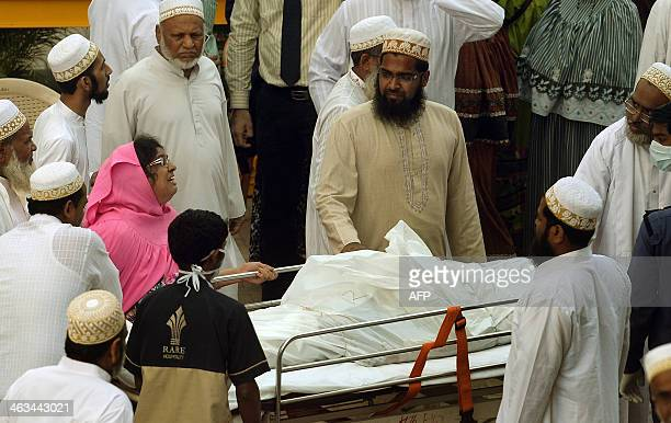 Indian Bohra Muslims gather around the body of a victim killed in a stampede inside the Saifee Hospital in Mumbai on January 18 2014 A stampede...