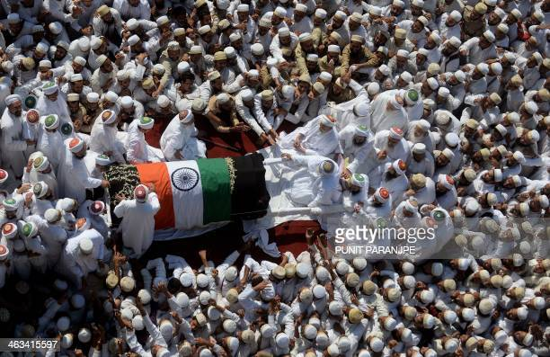 Indian Bohra Muslims gather around the coffin of their spiritual leader Syedna Mohammed Burhanuddin during his funeral procession in Mumbai on...