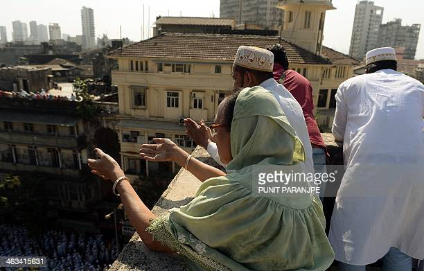 Indian Bohra Muslims pray as the funeral procession of their spiritual leader Syedna Mohammed Burhanuddin in Mumbai on January 18 2014 A stampede...