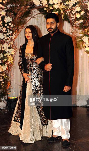 Indian Bollywood Abhishek Bachchanand actress Aishwarya Rai Bachchan pose as they attend a reception after the wedding of fellow thespians Bipasha...