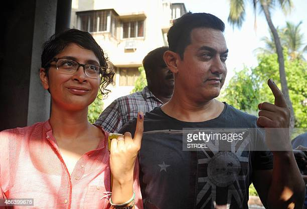 Indian Bollywood actor Aamir Khan and his wife Kiran pose for a photograph after casting their vote at a polling station in Mumbai on April 24 2014...