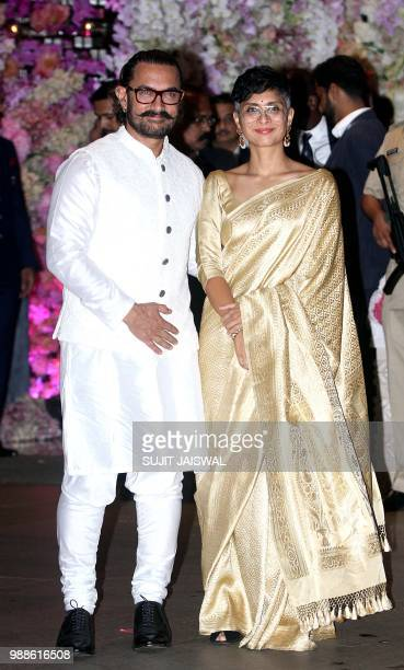 Indian Bollywood actor Aamir Khan poses for a picture with his wife Kiran Rao Khan as they attend the preengagement party of India's richest man and...