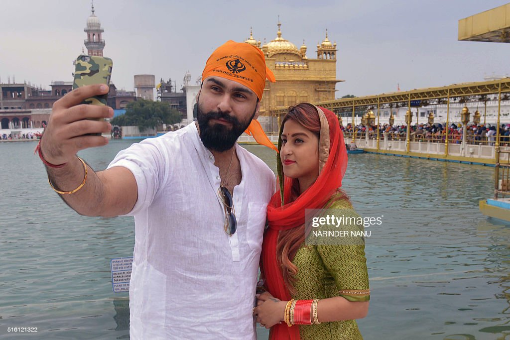 Indian Bollywood actor Aarya Babbar and his wife Jasmine Puri take a selfie photograph as they visit the Golden Temple in Amritsar on March 17 2016 /.