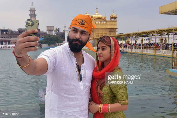 Indian Bollywood actor Aarya Babbar and his wife Jasmine Puri take a selfie photograph as they visit the Golden Temple in Amritsar on March 17 2016 /...