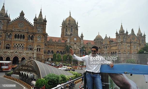 Indian Bollywood actor Abhishek Bachchan gestures as he stands on top of a bus during a promotional event for the forthcoming film 'Raavan' while...