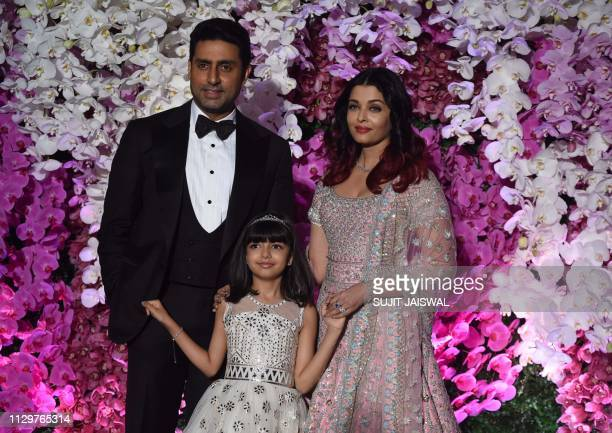 Indian Bollywood actor Abhishek Bachchan poses for photographs along with his wife and actress and model Aishwarya Rai Bachchan and their daughter...