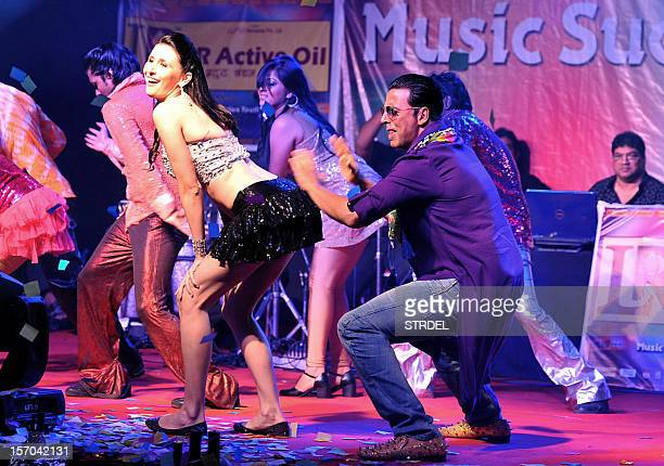 """Indian Bollywood actor Akshay Kumar dances with German model Claudia Ciesla during a promotional event for the forthcoming Hindi film """"Khiladi 786""""..."""