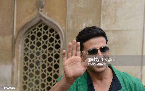 Indian Bollywood actor Akshay Kumar waves during a visit to the Charminar monument as he promotes his upcoming film BOSS in Hyderabad on October 11...