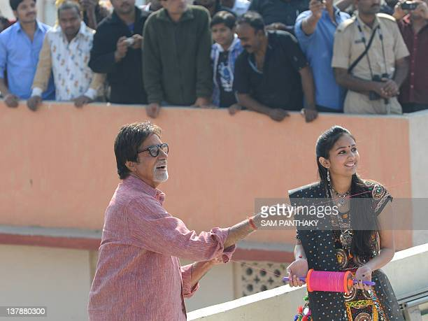 Indian Bollywood actor Amitabh Bachchan is assisted by Mansi Chowksi as he flies a kite on a terrace at Kameshwar nipole the walled city area of...