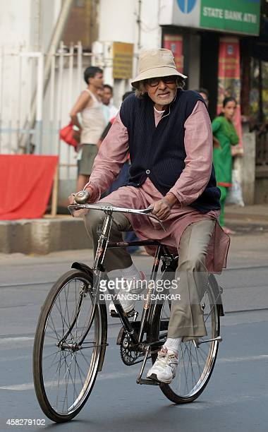 Indian Bollywood actor Amitabh Bachchan rides a bicycle along a road during filming for a movie in Kolkata on November 2 2014 AFP PHOTO/Dibyangshu...