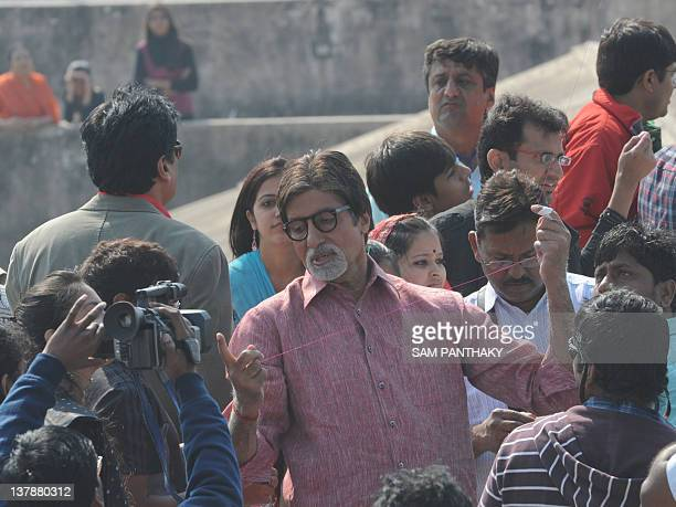 Indian Bollywood actor Amitabh Bachchan shows his cut finger as he flies a kite on a terrace at Kameshwar nipole the walled city area of Ahmedabad on...
