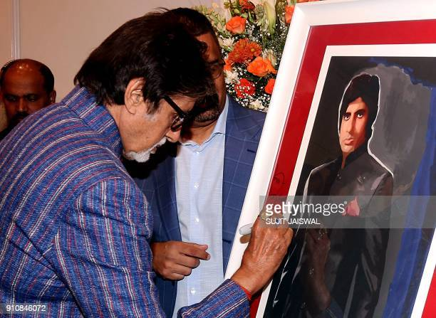 Indian Bollywood actor Amitabh Bachchan signs a painting during the exhibition 'Celebration of The Unexpected' of the artist Dilip De in Mumbai on...