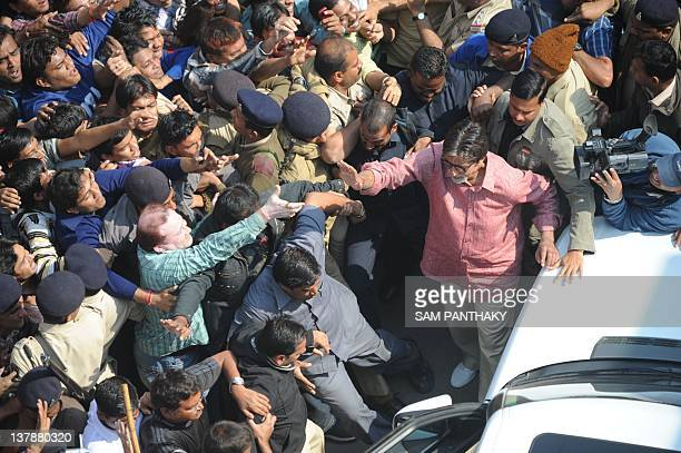 Indian Bollywood actor Amitabh Bachchan waves to fans after flying a kite on a terrace at Kameshwar nipole the walled city area of Ahmedabad on...