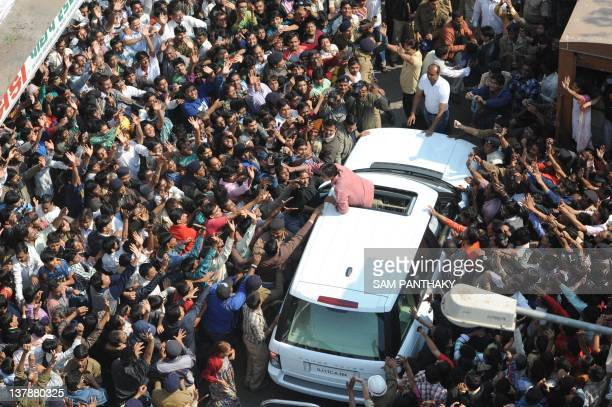 Indian Bollywood actor Amitabh Bachchan waves to fans from the sunroof of a car after flying a kite on a terrace at Kameshwar nipole the walled city...