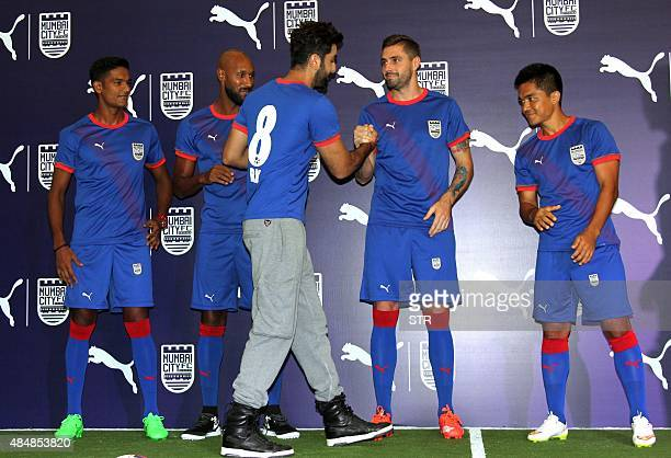 Indian Bollywood actor and coowner of Mumbai City Football Club Ranbir Kapoor shakes hands with Brazil's Andre Mortiz as France's Nicolas Anelka...