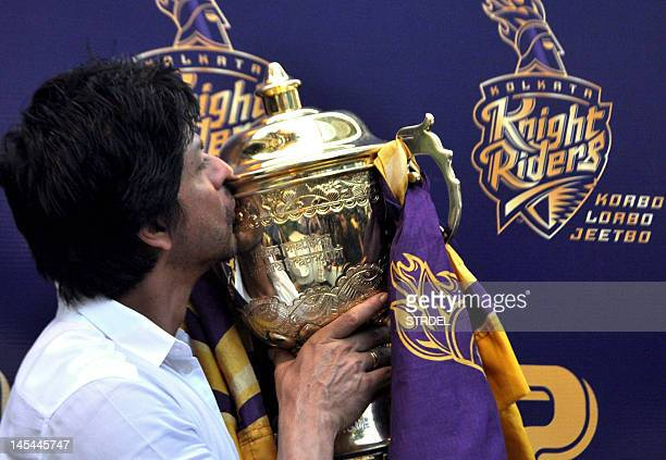 Indian Bollywood actor and Indian Premier League franchise Kolkata Knight Rider's coowner Shah Rukh Khan kisses the IPL trophy during a press...