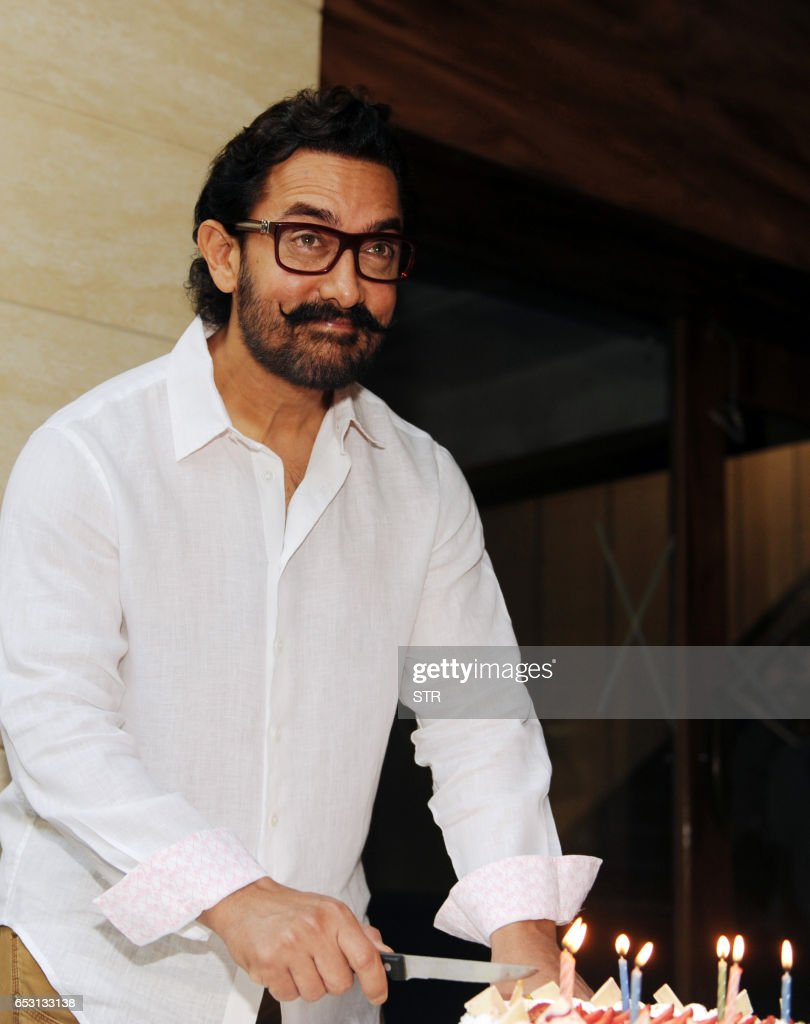 Indian Bollywood actor and producer Aamir Khan poses for the media during the cake cutting on his 52nd birthday, at his residence in Mumbai on March 14, 2017. /