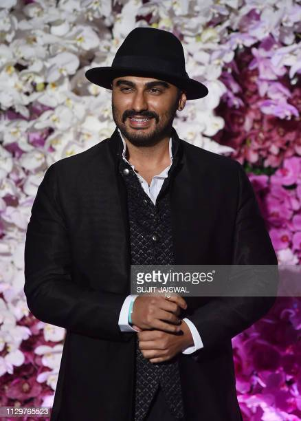 Indian Bollywood actor Arjun Kapoor poses for photographs as he arrives to attend the wedding reception of Akash Ambani son of Indian businessman...