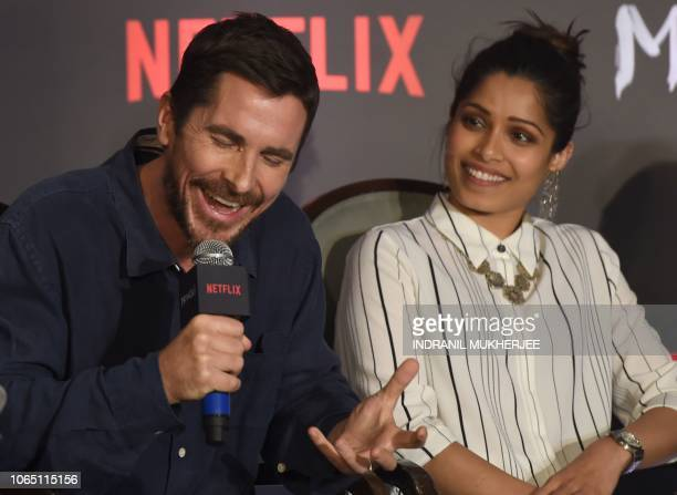Indian Bollywood actor Freida pinto looks on as US actor Christian Bale laughs during a press conference for Netflix's 'Mowgli Legend of the Jungle'...