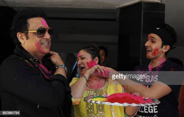 Indian Bollywood actor Govinda with his wife Sunita and son Yashvardhan Ahuja take part in celebrations to mark the Hindu festival of Holi in Mumbai...