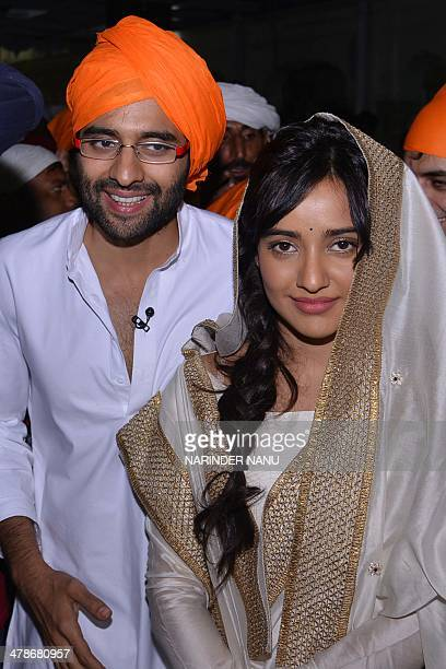 Indian Bollywood actor Jackky Bhagnani and actress Neha Sharma pay respects at the Sikh Shrine Golden temple in Amritsar on March 14 2014 Actors...