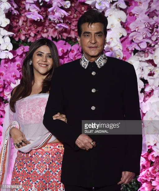 Indian Bollywood actor Jeetendra poses for photographs along with his daughter producer Ekta Kapoor as they arrive to attend the wedding reception of...