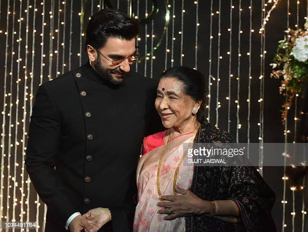 Indian Bollywood actor Ranbir Kapoor and playback singer Asha Bhosle pose for a picture during the wedding reception party of actress Priyanka Chopra...