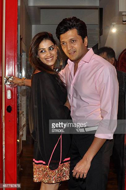 Indian Bollywood actor Riteish Deshmukh poses with his wife actress Genelia D'Souza as they attend the opening of a luxury boutique in Mumbai late...