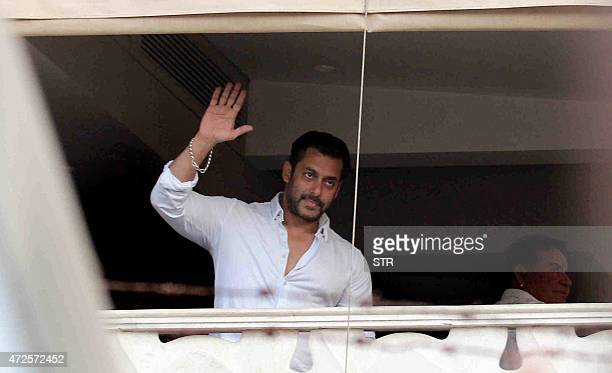 Indian Bollywood actor Salman Khan waves from the balcony on arrival at his house in Galaxy Apartment after getting bail from his ongoing trial of...