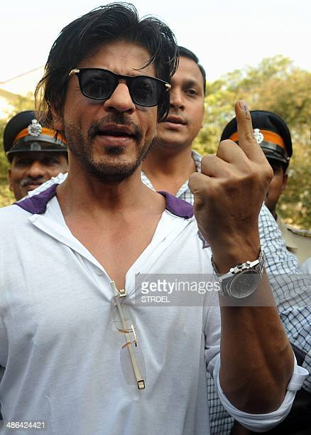 Indian Bollywood actor Shah Rukh Khan gestures with his inked finger as he leaves after casting his vote in national elections at a polling station...