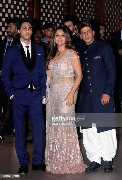 Indian Bollywood actor Shah Rukh Khan poses for a picture with his wife Gauri Khan and son Aryan Khan as they attend the preengagement party of...