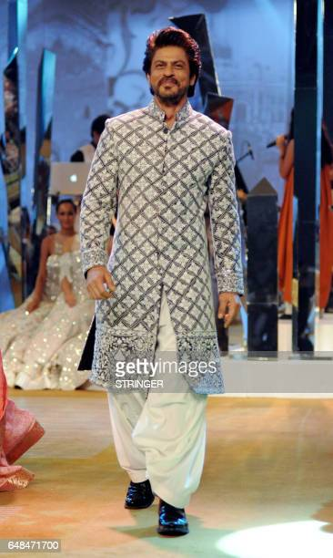Indian Bollywood actor Shah Rukh Khan showcases a creation by designer Manish Malhotra at the fundraiser Mijwan 2017 fashion show in Mumbai on March...