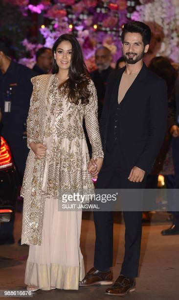 Indian Bollywood actor Shahid Kapoor pose for a picture with his wife Mira Rajput as they attend the preengagement party of India's richest man and...