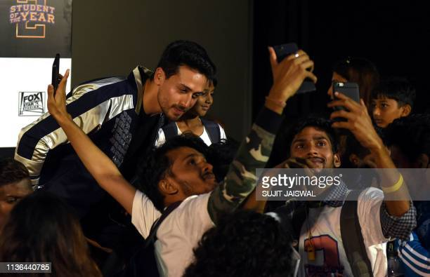Indian Bollywood actor Tiger Shroff poses for photographs along with fans during the trailer launch of his upcoming romantic comedy drama Hindi film...