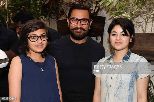 Indian Bollywood actors Aamir Khan Suhani Bhatnagar and Zaria Wasim pose for a photograph during a promotional event for the forthcoming Hindi film...
