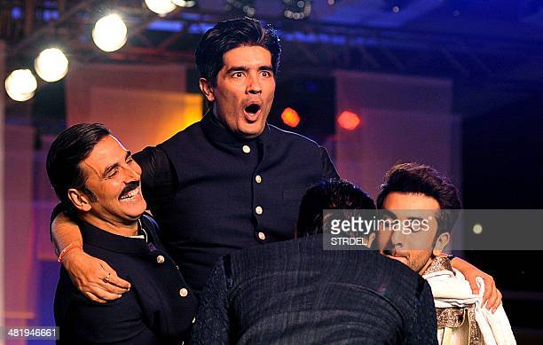Indian Bollywood actors Akshay Kumar Siddharth Malhotra and Ranbir Kapoor lift designer Manish Malhotra as they model creations by Malhotra during a...